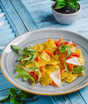 Ravioli de espinafre e ricota com queijo parmesão, tomate seco, rúcula