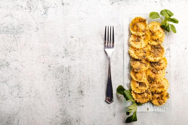 Ravioli de massa recheada italiana com fundo de molho pesto