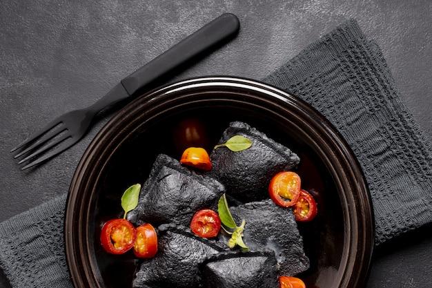 Ravioli de vista superior do close-up preto e fatias de tomate