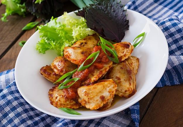 Ravioli delicioso com molho de tomate e cebola verde