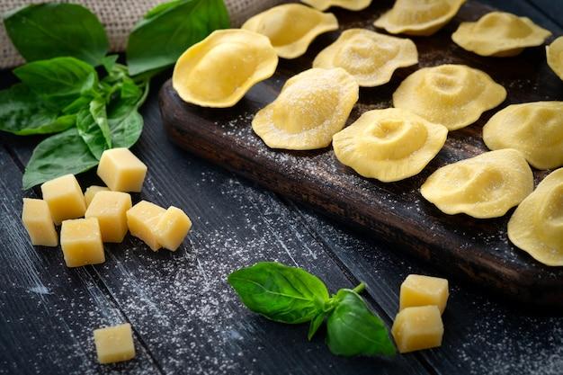 Ravioli fresco com queijo e manjericão polvilhado com farinha na placa de madeira