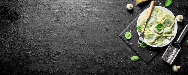 Ravioli italiano com cogumelos e folhas de espinafre. em preto rústico