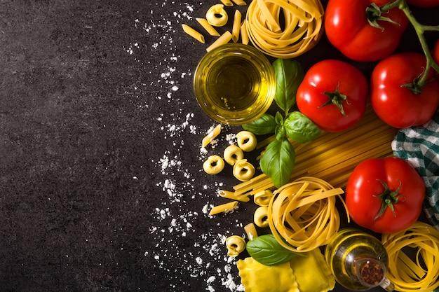 Ravioli, macarrão penne, espaguete, tortellini, tomate e manjericão no preto. vista superior, espaço de cópia