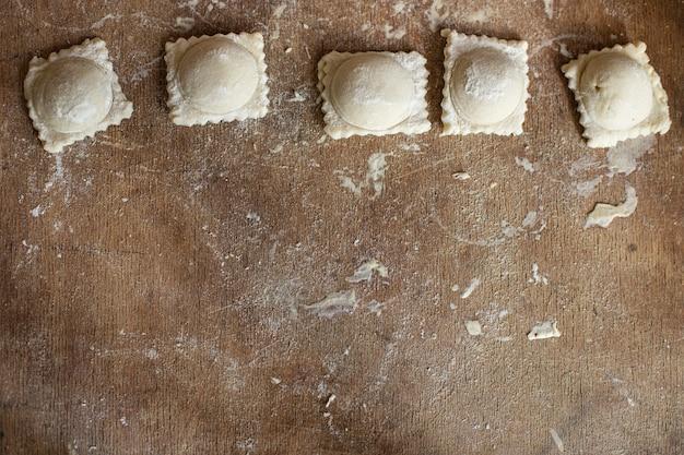 Ravioli massa crua enchendo bolinhos quadrados na mesa refeição saudável cópia espaço comida fundo