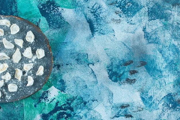 Ravioli turco cru no tabuleiro, na mesa azul.