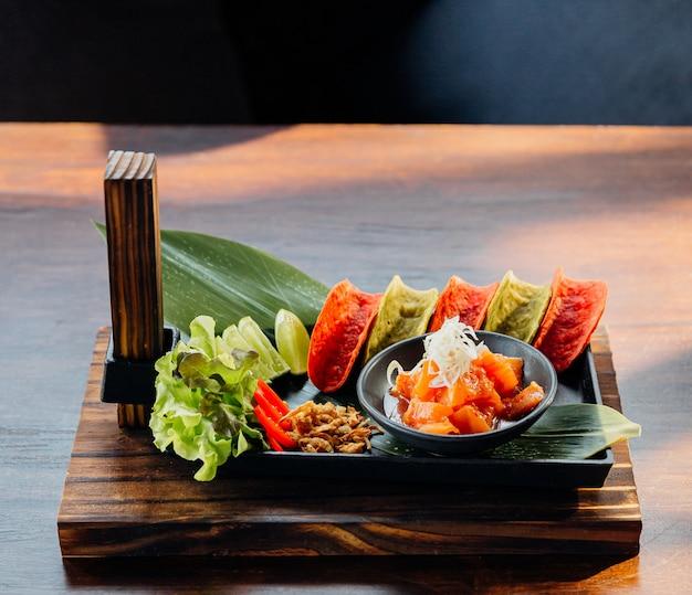 Raw salmon spicy salad servido com as microplaquetas crocantes vermelhas e verdes para o canape.