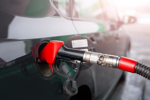 Reabastecer um carro com gasolina ou óleo diesel em um posto de gasolina.