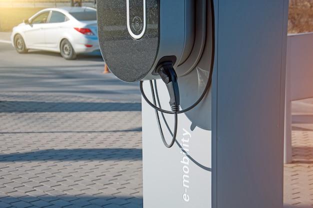 Reabastecimento para e-mobilidade de carros elétricos, o plugue elétrico sob tensão restaura a carga da bateria.