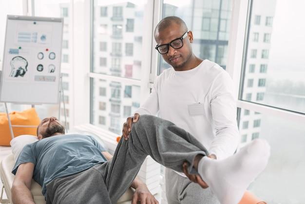 Reabilitação física. fisioterapeuta inteligente em pé perto de seu paciente enquanto levanta sua perna