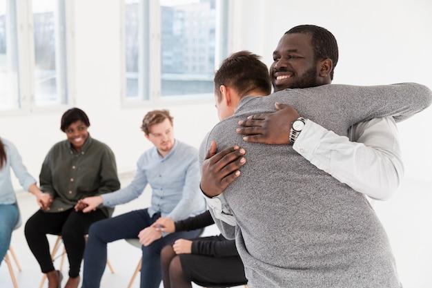Reabilitação sorrindo pacientes abraçando uns aos outros