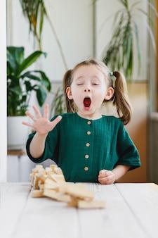 Reação expressiva da menina em idade pré-escolar na queda inesperada da torre do bloco de madeira. vertical.