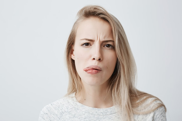 Reação humana negativa, sentimentos e atitudes. retrato do close-up da mulher loira melindrosa enojada em casual wear fazendo careta, saindo da língua, sentindo náuseas por causa de mau cheiro ou fedor