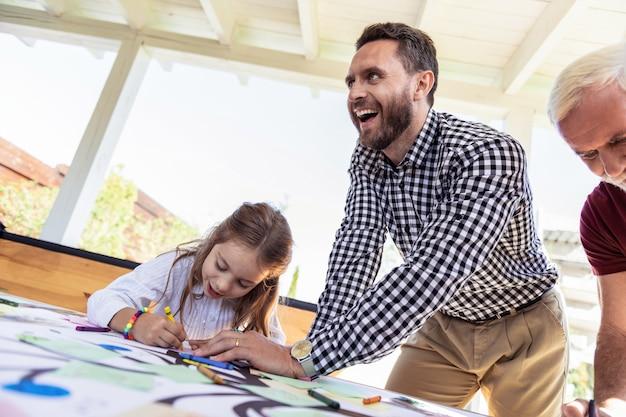 Reação positiva. criança séria curvando a cabeça enquanto desenha