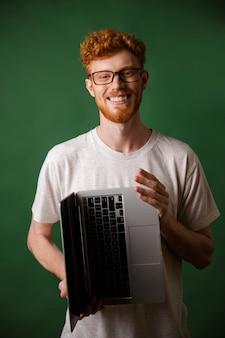 Readhead alegre homem barbudo de óculos e camiseta branca, segurando o laptop nas mãos