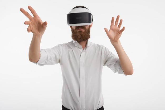 Realidade aumentada, inovações, programação e conceito de futuro. homem com barba por fazer e barba por fazer posando com fone de ouvido vr, de mãos dadas na frente dele enquanto toca em algo