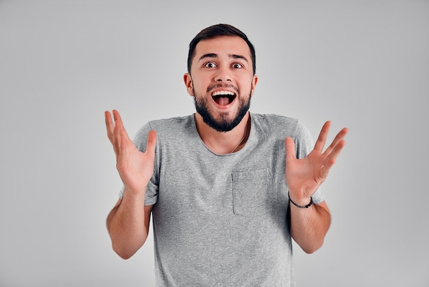 Realização, conceito de sucesso. um alegre homem caucasiano levanta as mãos, seus olhos estão cheios de felicidade, regozijando-se com suas grandes realizações. atraente homem negro vestido com uma camiseta cinza.
