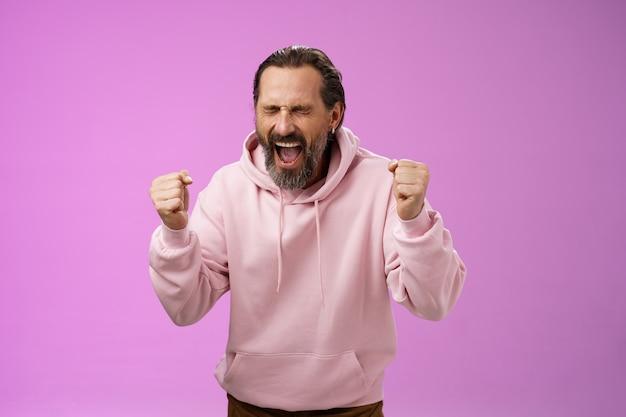 Realizado feliz, feliz, triunfando, maduro, barbudo, homem, cabelo grisalho, grisalho, gritando, sim, emocionado, alegremente, cerrar os punhos celebrando o sucesso ganhar na loteria se tornar milionário, em pé fundo roxo.