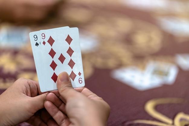 Reaw ver os closeup da mulher asiática cartão de jogo com dinheiro em cima da mesa sobre o tapete