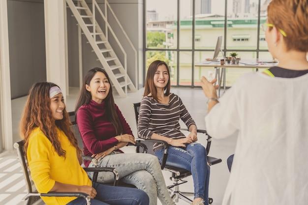 Reaw vista da mulher asiática sênior gerente apresentando as idéias criativas para mulher criativa
