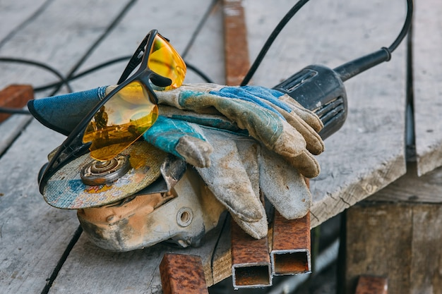 Rebarbadora, óculos de segurança, luvas, um pedaço de cano. ferramentas de trabalho