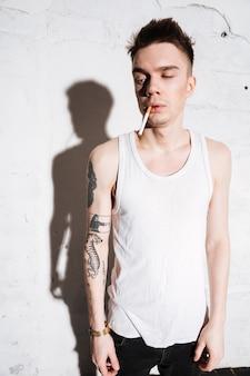 Rebelde tatuado homem fumando