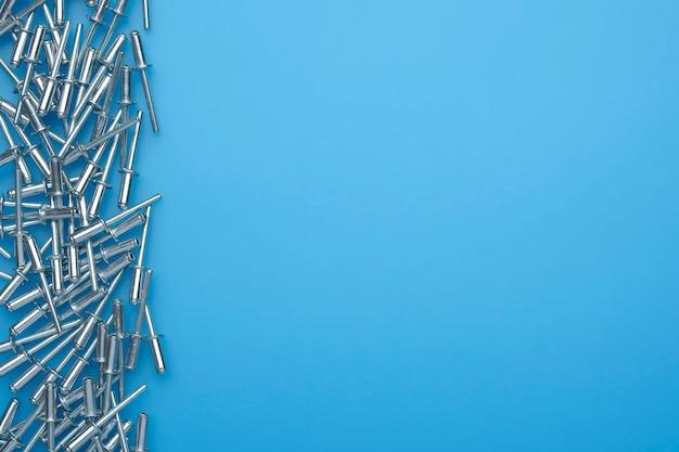 Rebites de metal em fundo azul. rebites caindo. copie o espaço para o texto.