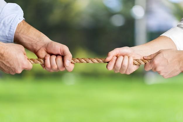 Rebocador, dois empresários puxando uma corda em direções opostas isoladas no fundo da natureza