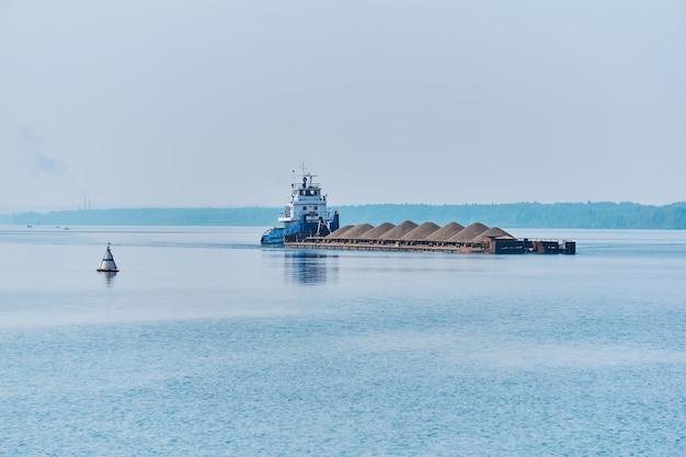 Rebocador empurra uma barcaça de carga a granel com areia no rio na névoa da manhã