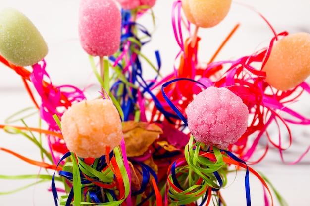 Rebuçados e bombons coloridos em varas com serpentina inventam sua receita doce saborosa e brilhante