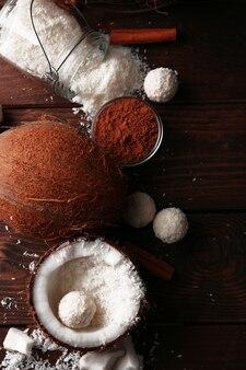 Rebuçados em flocos de coco e ingredientes em madeira escura