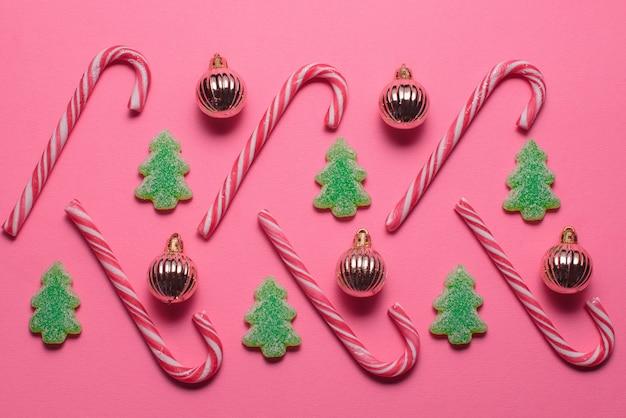 Rebuçados em forma de árvore de natal e bolas douradas repousam sobre um fundo rosa, vista superior. conceito de natal e ano novo