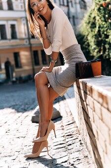 Recebendo bons feedbacks. mulher jovem e atraente falando ao telefone inteligente e sorrindo enquanto está sentado ao ar livre