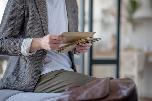 Recebendo e-mails. um homem abrindo e verificando envelopes com e-mails