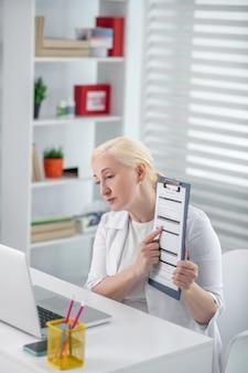 Receita, aconselhamento online. médica, sentado no seu local de trabalho, mostrando uma receita em uma tela de laptop, atencioso sério.