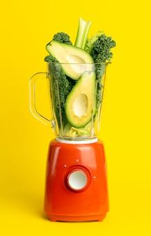Receita de batido. smoothie verde de legumes (abacate, aipo, salada de cale, espinafre) no liquidificador em um fundo amarelo. vegan e conceito de desintoxicação de alimentos saudáveis