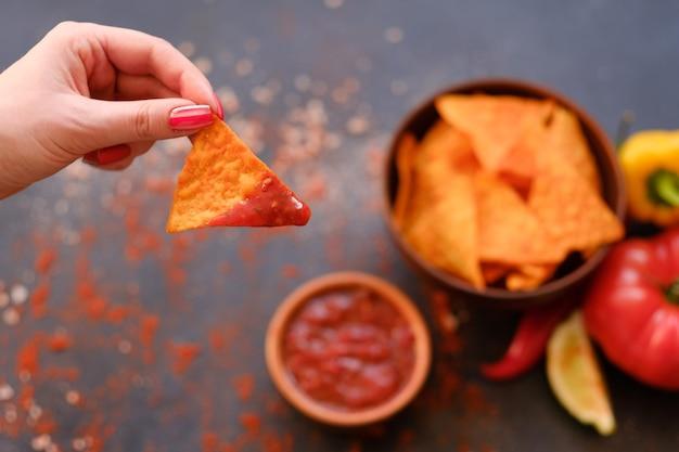 Receita de chips de nacho de tortilla. batatas fritas naturais em uma tigela. mão de uma mulher segurando uma fatia triangular crocante picante mergulhada em molho de tomate