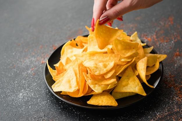 Receita de comida de chips de nacho de tortilla. mão de uma mulher pegando uma fatia de batata frita natural de um prato