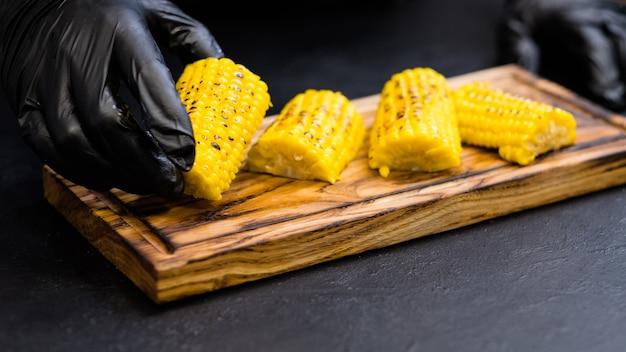 Receita de comida vegetal. foto recortada do chef servindo milho bonduelle assado em pedaços de espiga com manteiga derretida.
