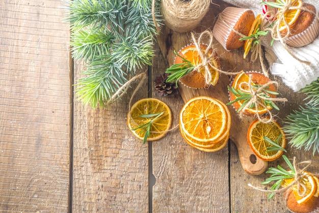 Receita de cozimento caseiro de natal de inverno. muffins picantes, cupcakes de laranja, raspas de frutas cítricas, alecrim e especiarias. sobre uma mesa de madeira com galhos de pinheiro