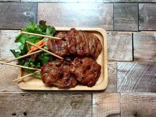 Receita de espetos de porco grelhado moo ping na placa de madeira