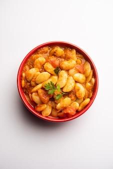 Receita de sabzi ou sabji de curry de feijão duplo feito com especiarias indianas básicas e tomates frescos servidos em uma tigela com foco seletivo