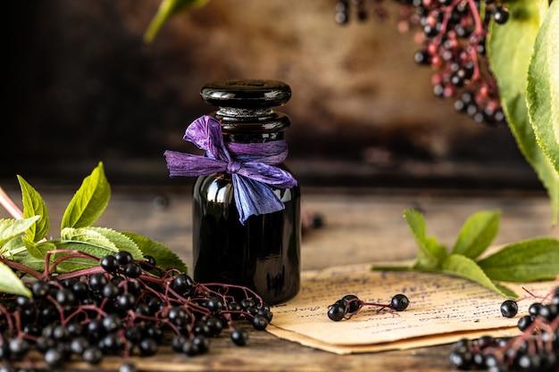 Receita de xarope de sabugueiro preto caseiro em uma garrafa de vidro sobre uma mesa de madeira. frutas frescas no fundo. copie o espaço