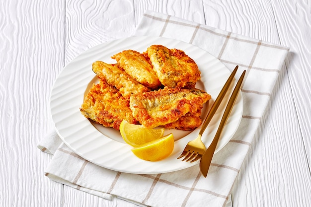 Receita deliciosa de filé de pescada frito empanado, servido em prato branco com fatias de limão, talheres dourados sobre superfície de madeira branca com guardanapo, close-up