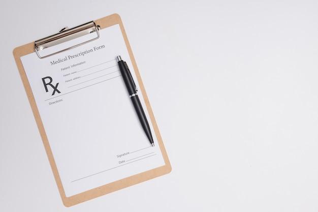 Receita médica vazia com uma caneta isolada. caneta esferográfica deitada na prescrição médica perto do estetoscópio no consultório médico.