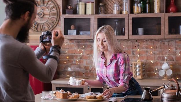 Receita online. blogging. mulher com produtos de sobremesa. homem filmando episódio de vlog sobre culinária de bolos e doces.