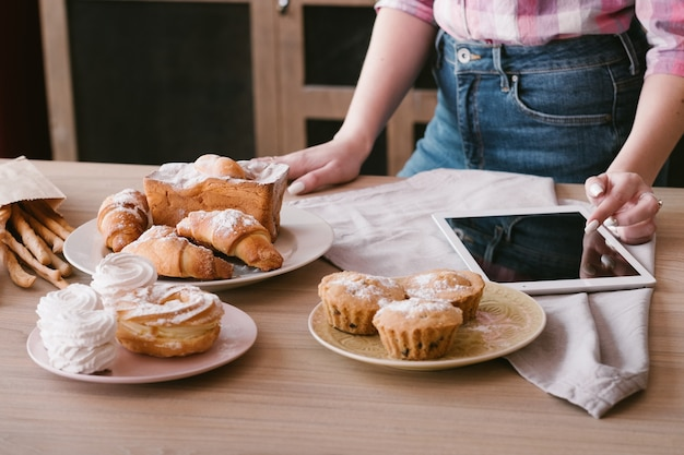Receita online. cozinhar bolos e pastelaria. mulher com tablet. doce padaria caseira ao redor.