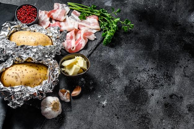 Receita para cozinhar batatas assadas. ingredientes bacon, manteiga, salsa e queijo. fundo preto. vista do topo. copie o espaço