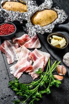 Receita para cozinhar batatas assadas. ingredientes bacon, manteiga, salsa e queijo. fundo preto. vista do topo