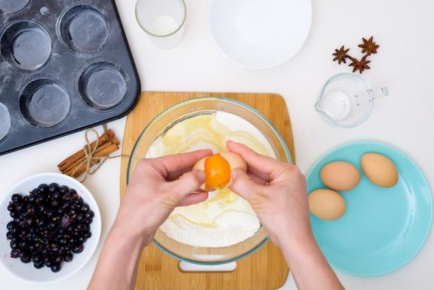 Receita passo a passo para bolos com groselhas. preparar a massa, misturando os ingredientes da farinha, manteiga, açúcar, ovos, baunilha, groselha. a vista do topo . cupcakes com recheio de groselha