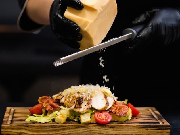 Receita tradicional italiana. foto colhida do chef ralando queijo parmesão em salada césar com filé de frango defumado e bacon.